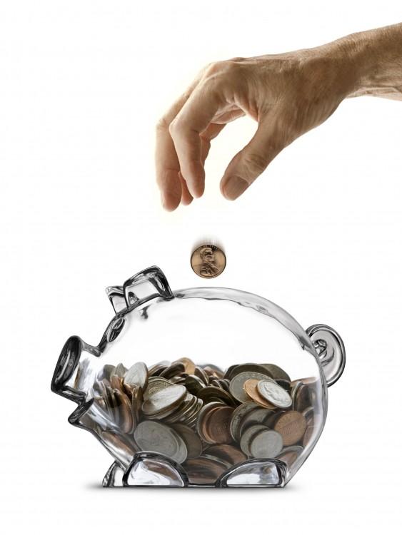 mano de una persona ahorrando en una alcancía