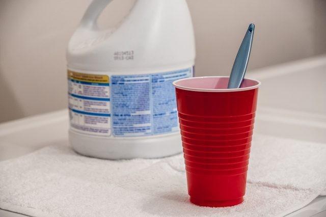 cloro y un vaso rojo con un cepillo dental en su interior sobre una lavadora