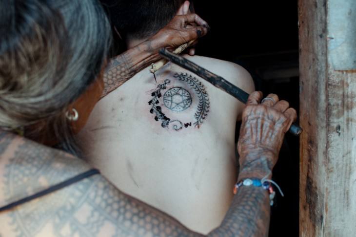 Whang-do tatuando a una persona con la técnica tradicional