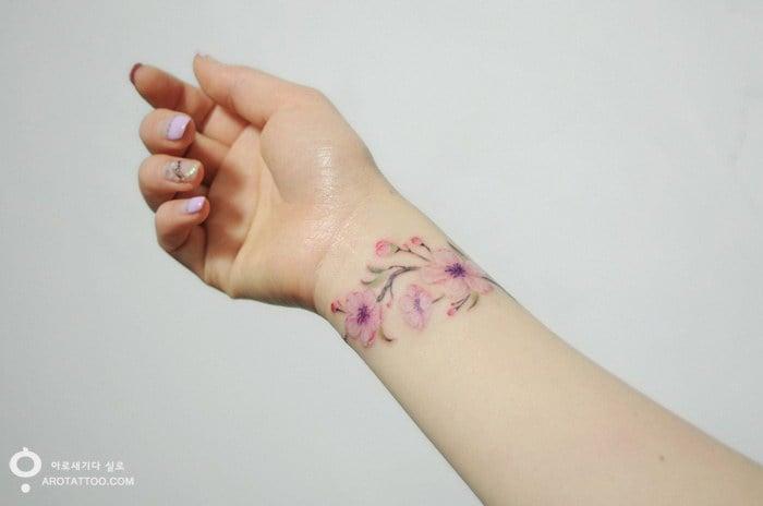 Tatuaje acuarela con un diseño floral sobre la muñeca