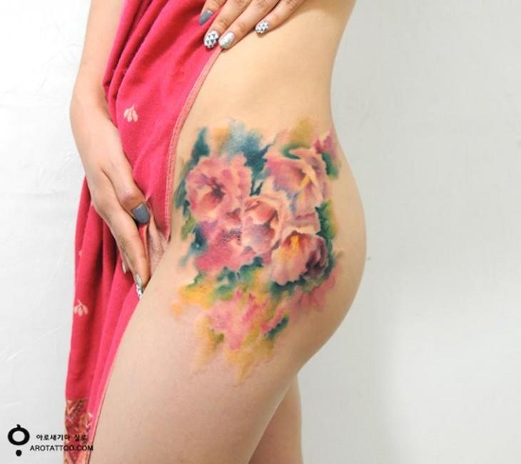 Tatuaje sobre el muslo de una mujer con un diseño floral
