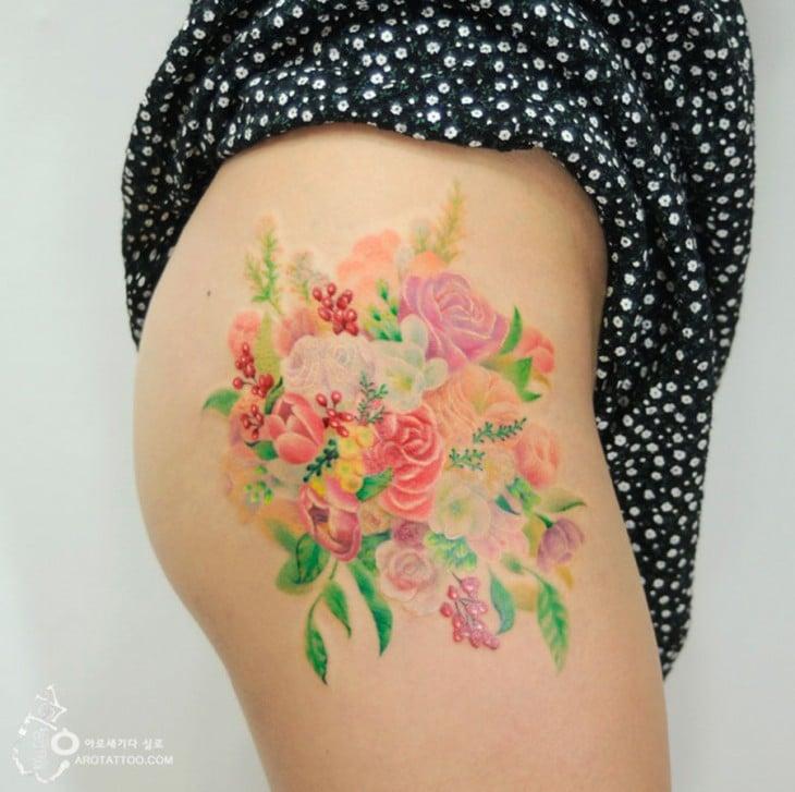 tatuaje acuarela con un diseño floral sobre un muslo