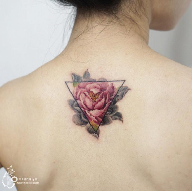 Tatuaje con el diseño de una flor detrás de un triángulo