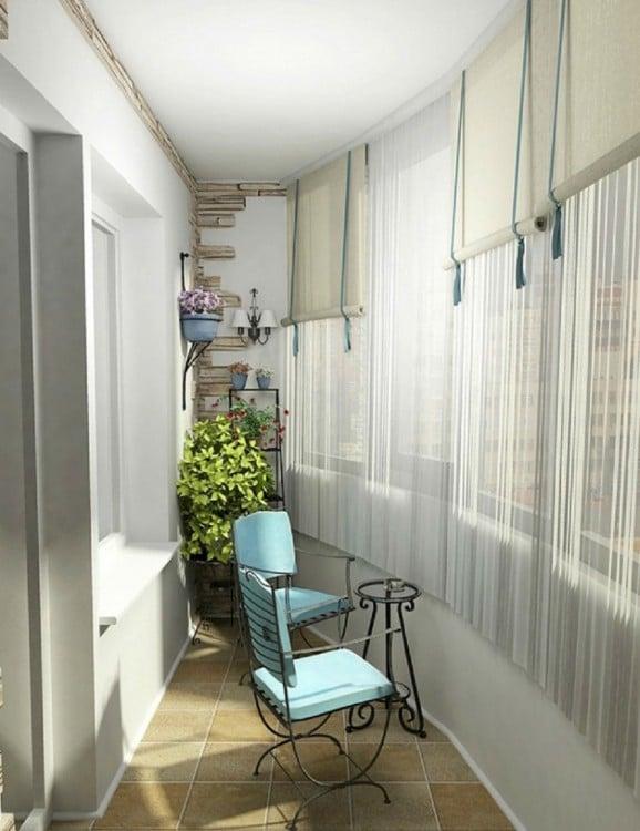 Balcón con silla mecedora azul, las cortinas tenues le dan un aspecto tradicionalista y cálido al sitio