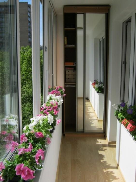 Balcón con flores y un espejo para añadir sensación de mayor espacio