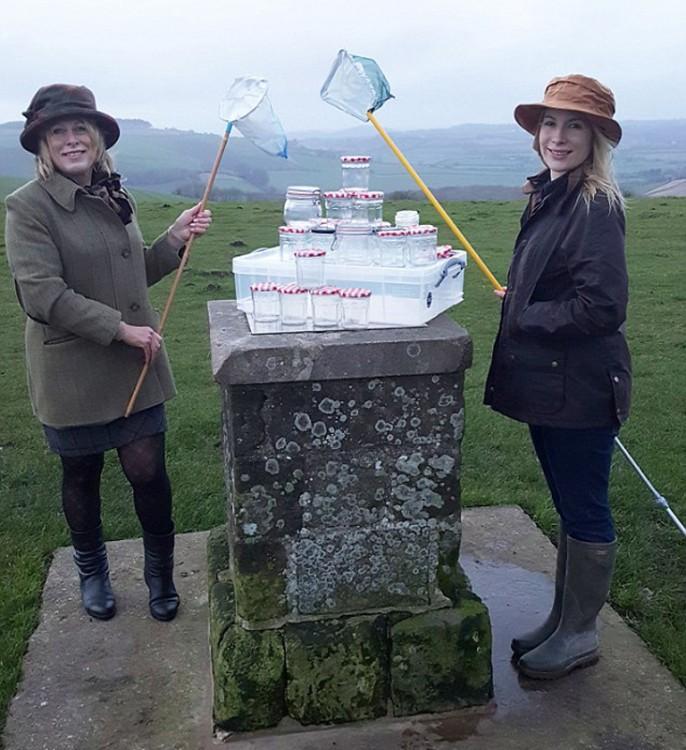 mujeres británicas con redes y muchos frascos de aire fresco apilados sobre una piedra