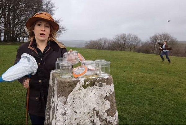 mujer con frascos transparentes en campos británicos