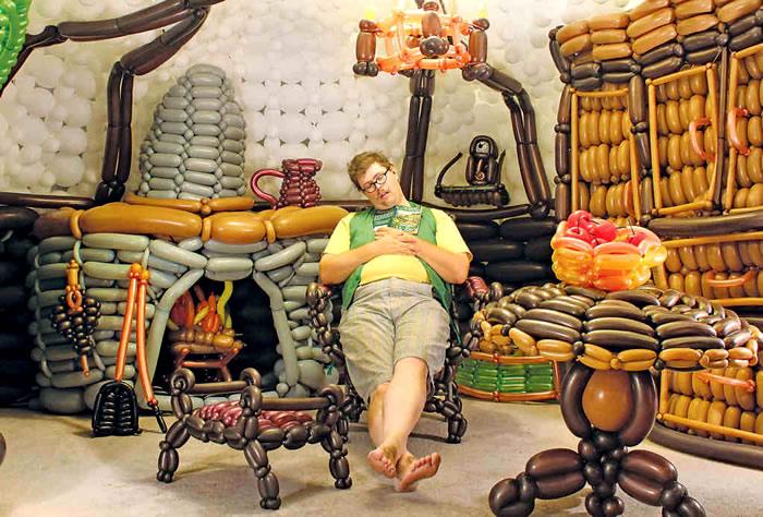 hombre sentado en una silla dentro del salón de la casa de el hobbit creada con globos