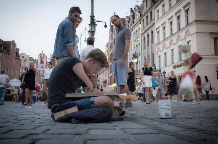 Mariusz Kedzierski sentado en una calle dibujando