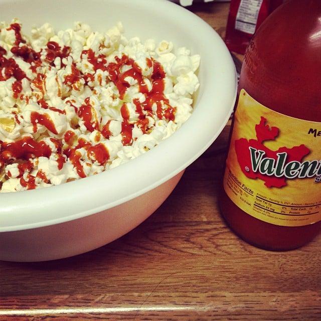 palomitas de maíz a lado de una botella de salsa valentina