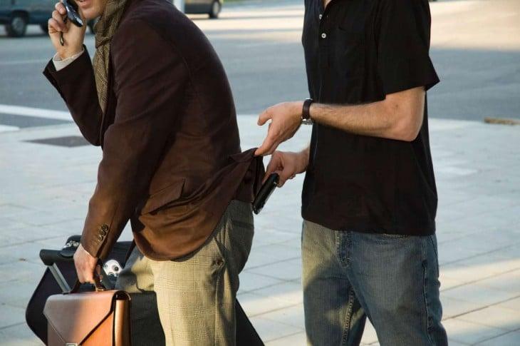 chico sacando la cartera de un hombre que va caminando por la calle