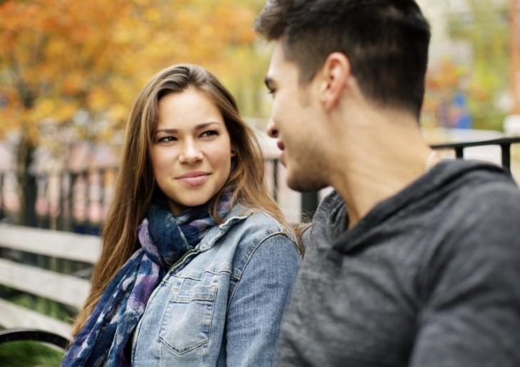 chica mirando fijamente a un chico frente a ella en una banca