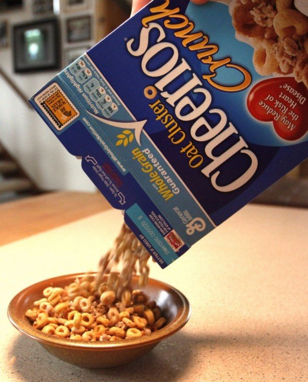 mano de una persona vaciando cereal sobre un plato