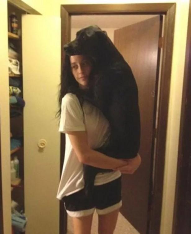 chica parada cargando a su perro