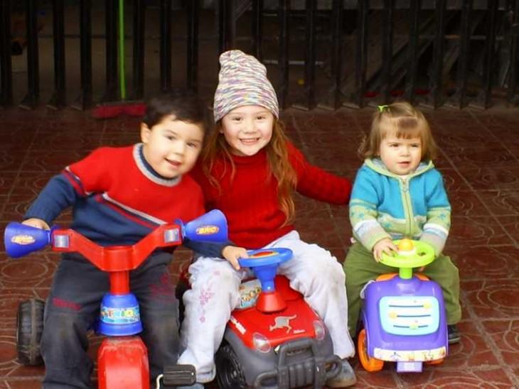 fotografía de tres niños en carritos jugando en la calle