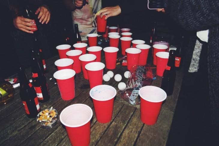 mesa de centro llena de botellas de cerveza y vasos rojos