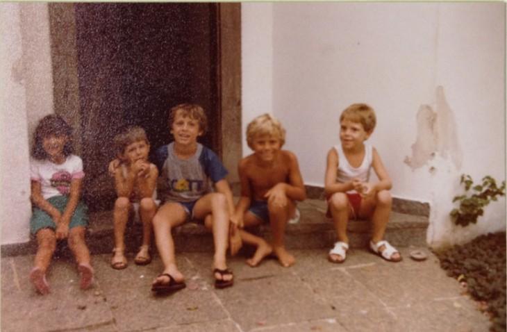 fotografía vieja de cinco niños sentados afuera de una casa