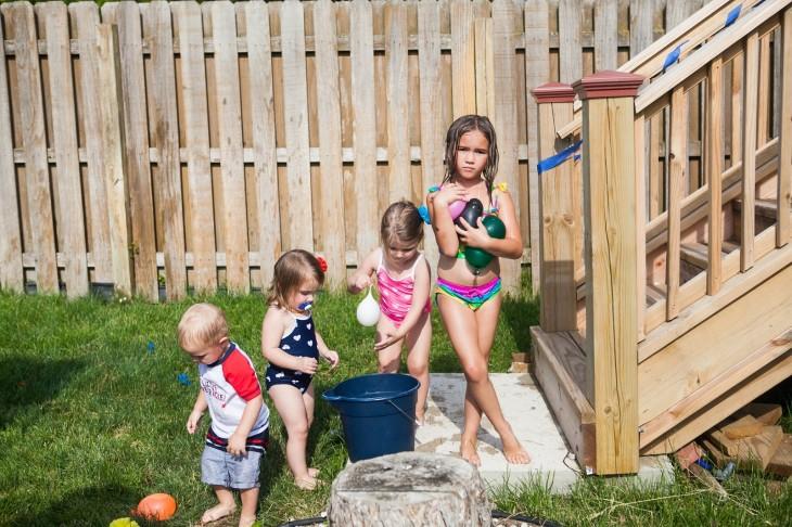 fotografía de cuatro niños en traje de baño con globos llenos de agua