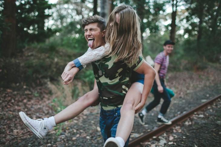 Chico cargando a una chica en su espalda
