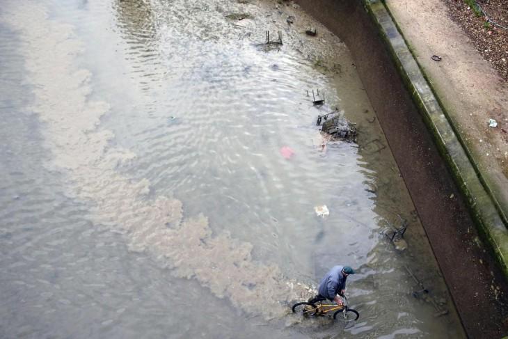 hombre sacando una bicicleta de un canal contaminado en parís
