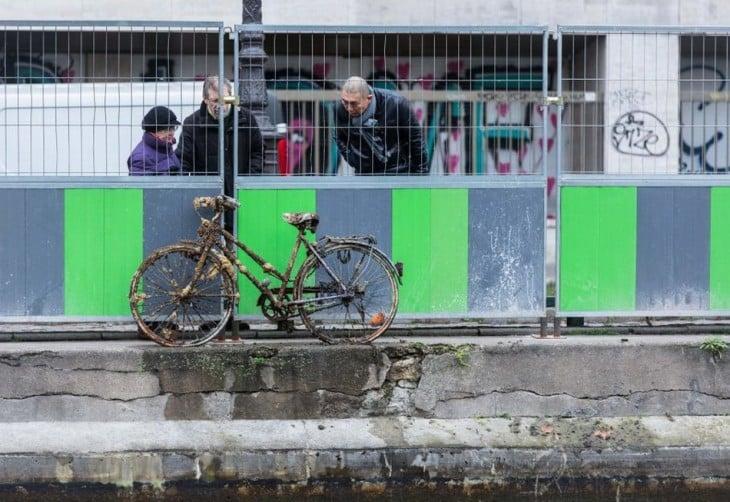 personas a la orilla del canal Saint-Martin en París viendo una bicicleta abandonada