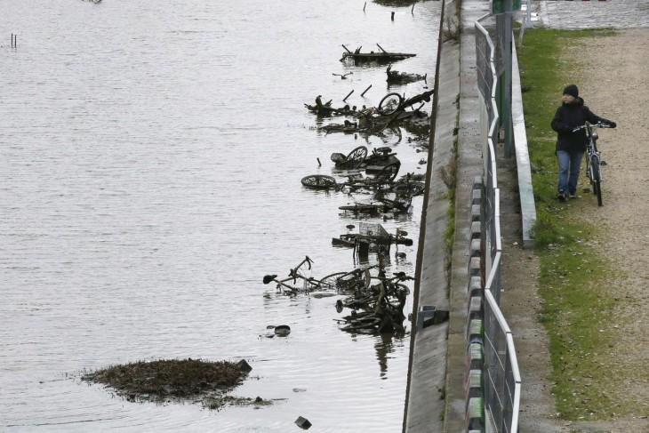 chica en bicicleta caminando a lado del canal saint-martin
