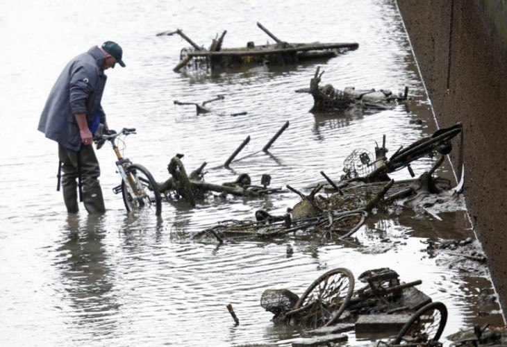 Hombre en París checando muchas bicicletas hundidas en el canal de Saint-Martin en París