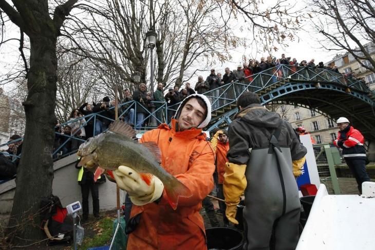 servidor público en París con un enorme pez en sus manos