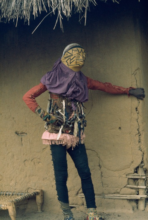 Personifying evil, a costumed mapico dancer in Mozambique hides from spectators, 1964.