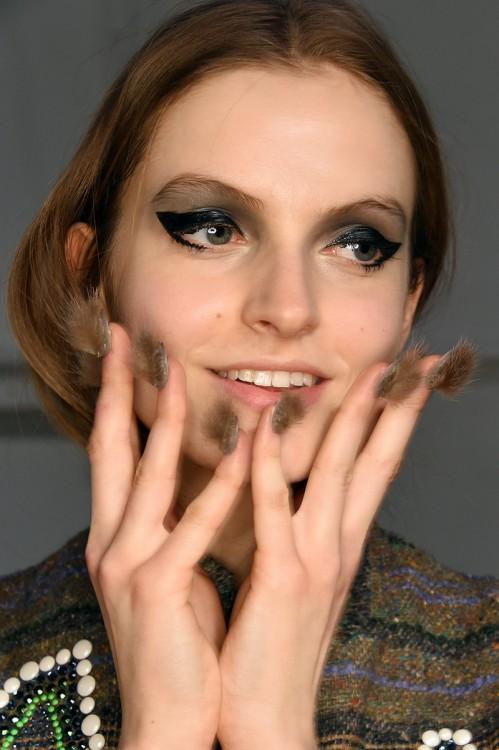 mujer con uñas peludas y las manos sobre su cara