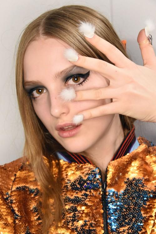 chica con la nueva tendencia de uñas peludas en color blanco sobre su cara