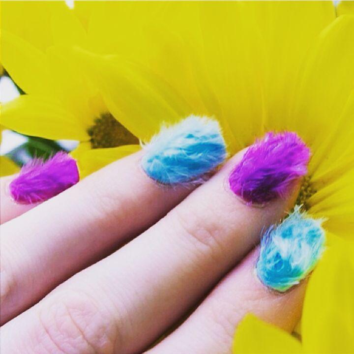 Uñas peludas de diferentes colores en la mano de una chica