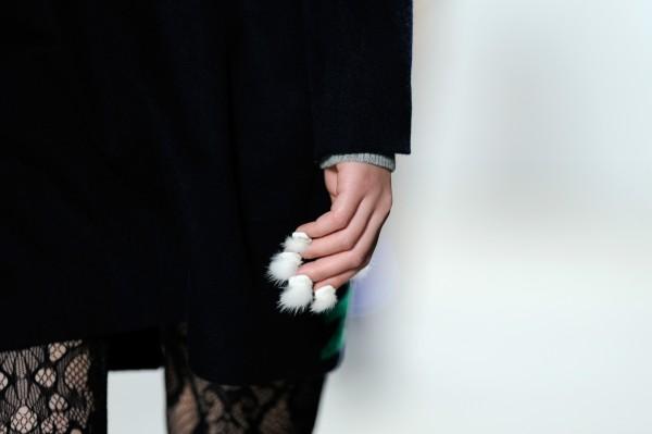 mujer caminando por una pasarela con uñas peludas en su mano