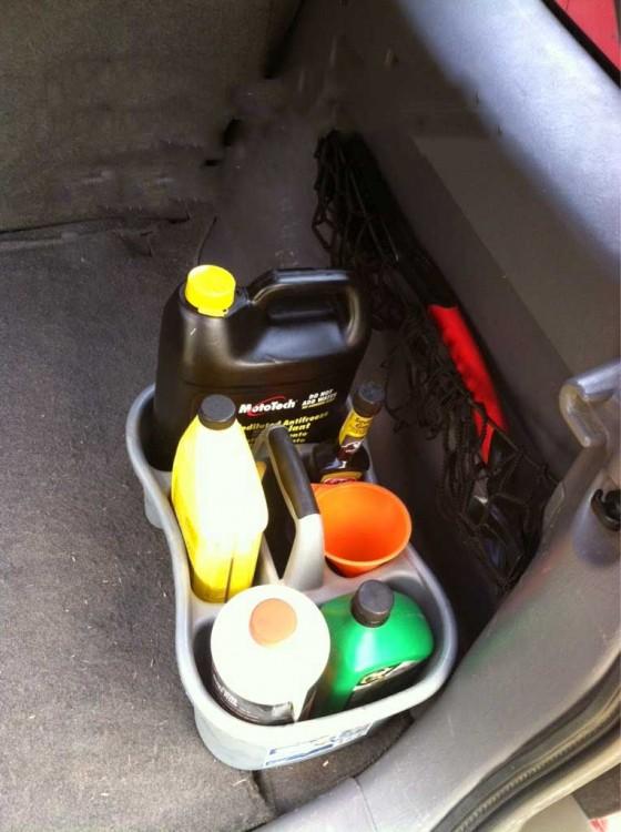 fluidos de un coche organizados dentro de una canasta de ducha