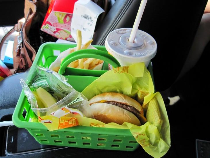 comida rápida organizada en una cesta de plástico dentro de un coche