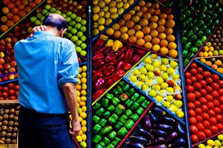 hombre viendo hacia un estante lleno de frutas y verduras perfectamente ordenadas