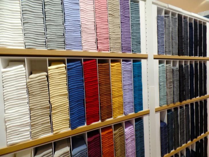 estantes de tienda comercial con camisetas ordenadas por colores