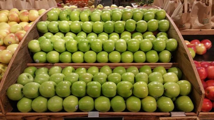 manzanas verdes ordenadas sobre un estante en un centro comercial