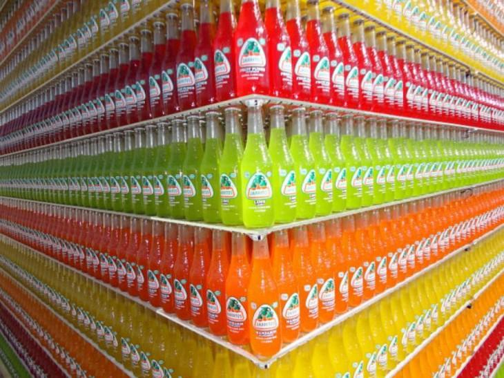 Botellas de vidrio de jarritos acomodadas por colores y sabores