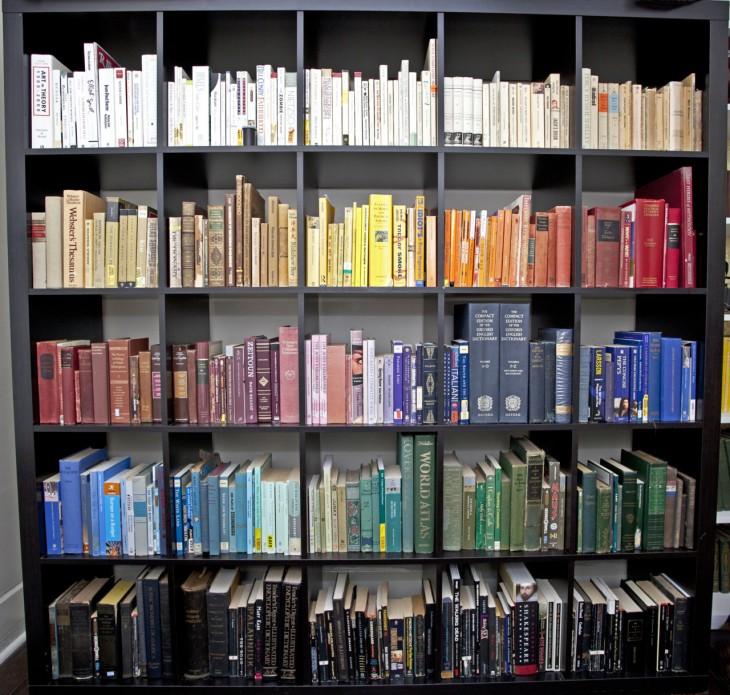 Librero lleno de libros ordenados por tamaños y colores