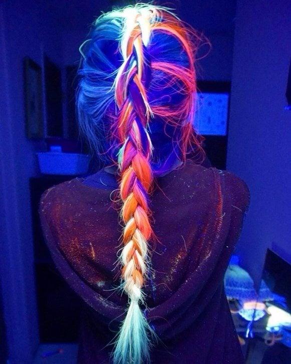 parte trasera de una chica mostrando su cabello multicolor que brilla en la oscuridad con una trenza