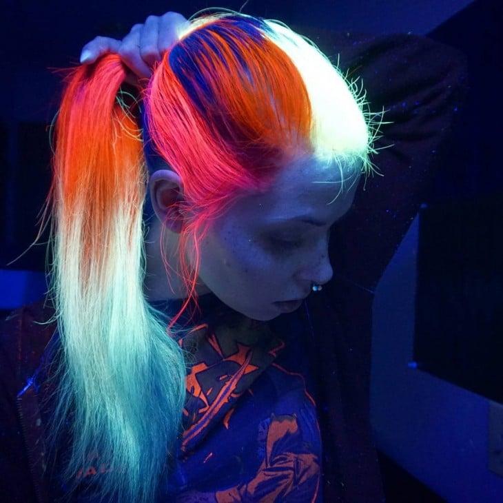chica sosteniendo su cabello que brilla en la oscuridad