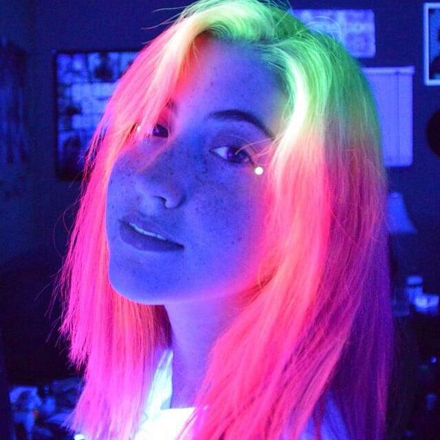 chica que muestra su cabello de colores que brilla en la oscuridad