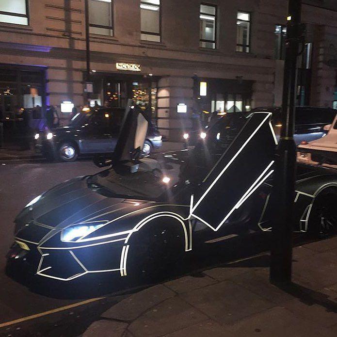 Carro lujoso rodeado de luces de neon en una de las calles de Londres