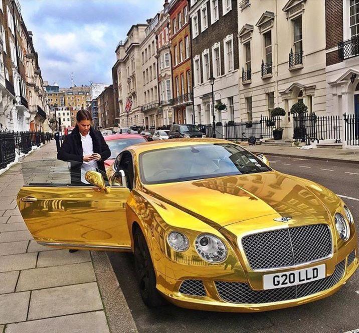 chico rico a punto de subirse a un lujoso coche en una de las calles de Londres