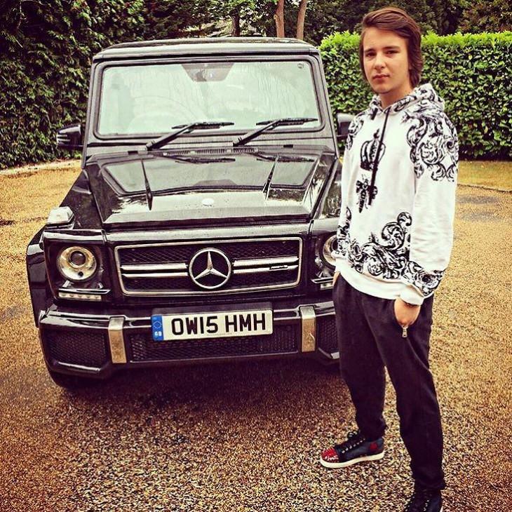 chico cerca de un coche lujoso a fuera de su casa