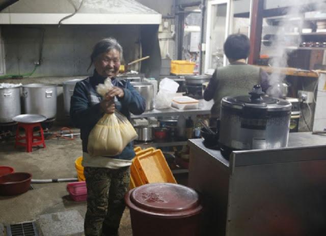Mujer coreana cargando una bolsa de comida en un restaurante