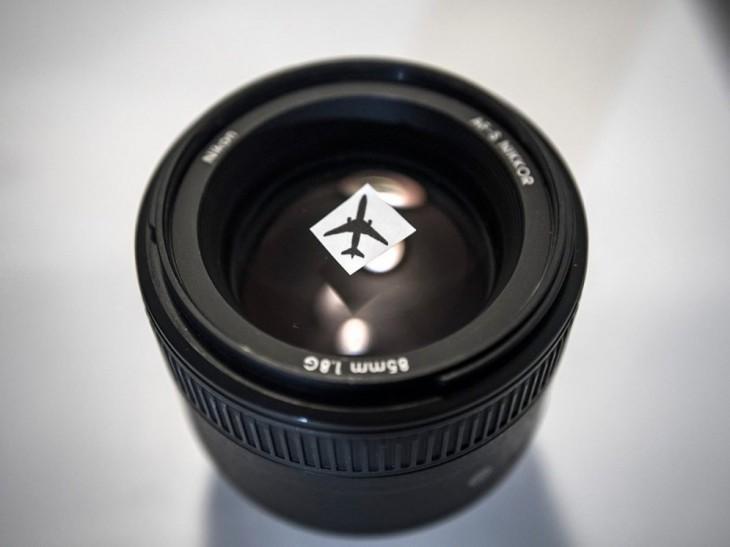 objetivo de una cámara nikon con un cuadro en el avión