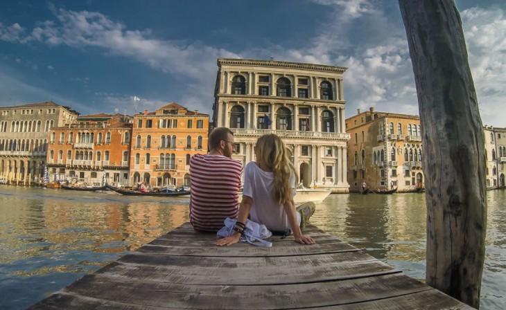 Pareja de Bloggers sentados en un muelle en Venecia, Italia