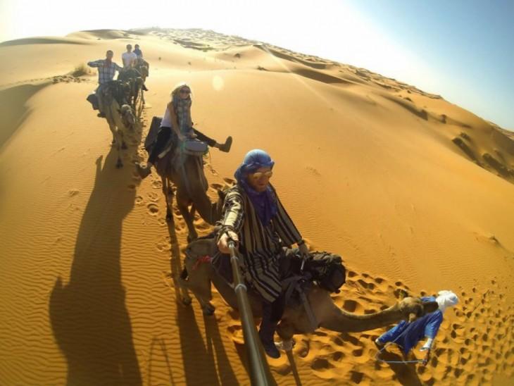 Selfie de personas sobre camellos en el desierto de el Sáhara